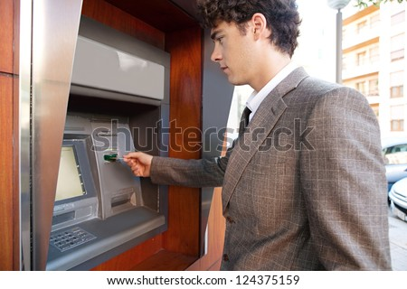 Side view of an elegant businessman withdrawing money from a wood decorated bank cash point, outdoors. - stock photo