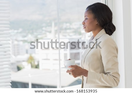 Side view of an elegant young businesswoman with tea cup looking through window in the office - stock photo
