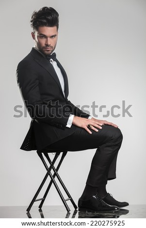 Side view of an elegant young man in tuxedo sitting on a stool, looking at the camera. - stock photo