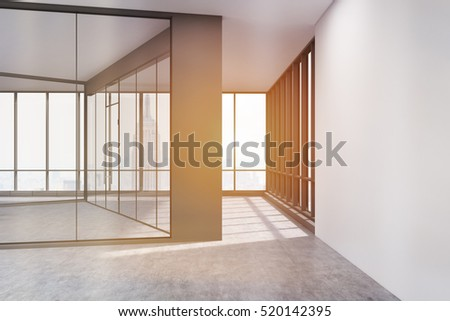 side view of an empty room with glass walls and concrete floor large panoramic windows