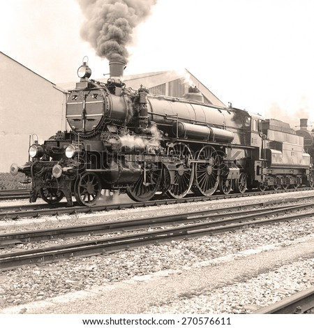 Side view of an old-fashioned steam locomotive in an austrian railway station. Scan from a B&W negative. - stock photo