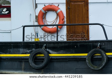 Side view of an old steel ship with lifebuoy in harbor. - stock photo