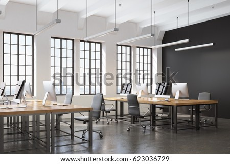 Side View Of An Open Space Office With A Black Wall Many Tables Computers