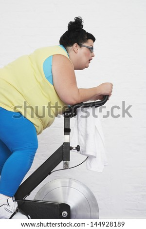 Side view of an overweight woman on exercise bike against white background - stock photo