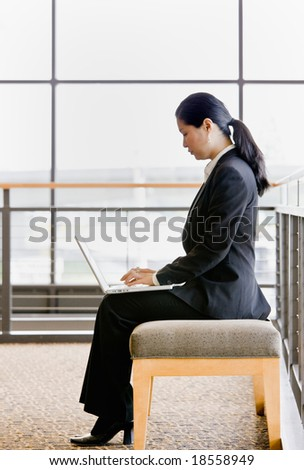 Side view of Asian businesswoman working on laptop in office lobby - stock photo