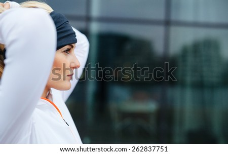 Side view of attractive female athlete ready of a run in city. Confident and motivated fitness woman looking away. - stock photo