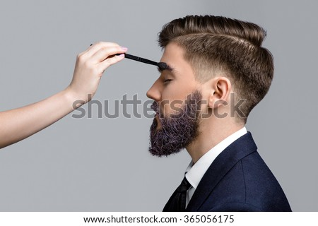 Side view of attractive man with violet beard and eyebrows, wearing in dark blue suit and tie, posing with closed eyes. Woman's hand with make-up brush near his face, on white background, in studio - stock photo