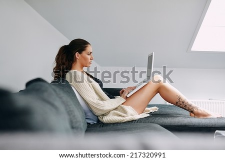Side view of attractive young lady sitting on sofa using laptop. Caucasian female model on couch surfing internet on laptop computer at home. - stock photo