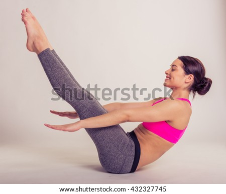 Side view of attractive young woman in sportswear doing exercises and smiling, on a gray background - stock photo