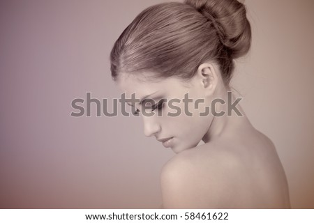 Side view of attractive young woman wearing a hair bun. She is pensively looking down. Horizontal shot. - stock photo