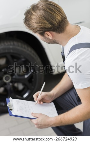 Side view of automobile mechanic writing on clipboard while examining car's wheel in workshop - stock photo