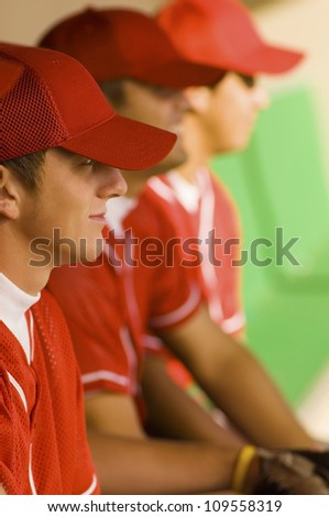 Side view of baseball players watching the game while sitting in dugout - stock photo