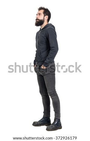Side view of bearded punker or hipster with hands in pockets looking up. Full body length portrait isolated over white studio background. - stock photo
