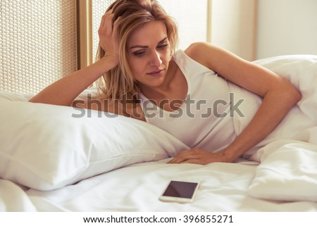 Side view of beautiful girl looking at a mobile phone while lying in bed - stock photo