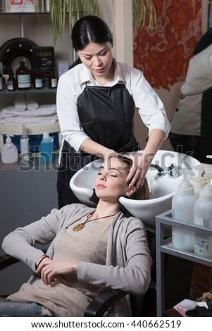 Side view of beautiful hairdresser washing hair to her client lady in hairdressing saloon. Client sitting with her eyes closed.