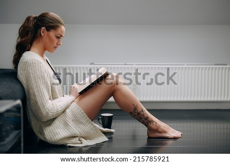 Side view of beautiful young lady reading a book. Caucasian female model at home sitting on floor by a couch with a novel. - stock photo