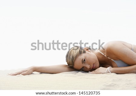 Side view of beautiful young woman looking away while sitting on sand dune at grassy beach - stock photo