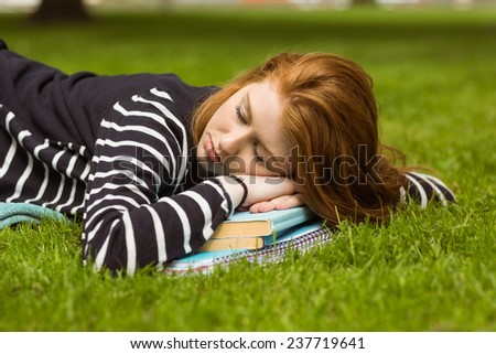 Side view of beautiful young woman lying on grass at the park - stock photo