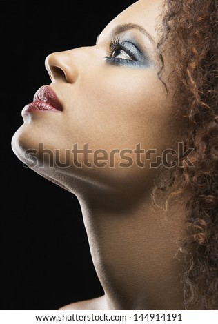 Side view of beautiful young woman wearing eye shadow on black background - stock photo