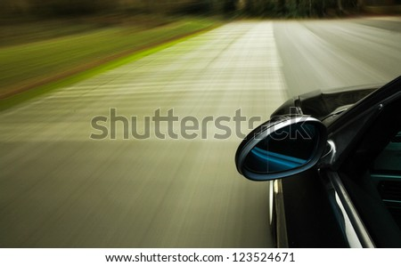 Side view of black car driving fast on the road - stock photo