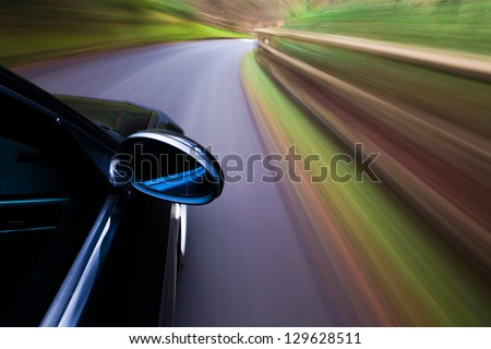 Side view of black car driving on the forest road. - stock photo