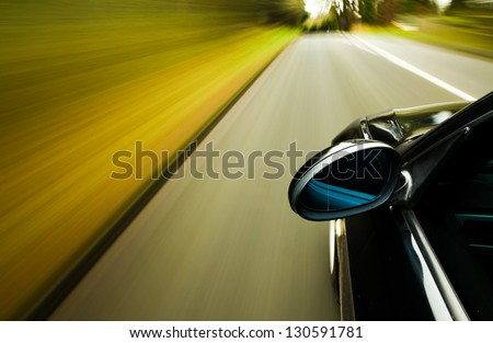 Side view of black car driving on the road with heavy blurred motion. - stock photo