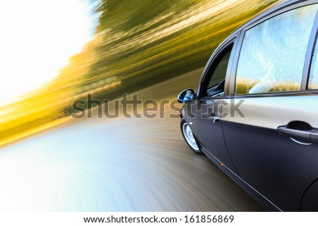 Side view of black luxury sedan with heavy blurred motion.