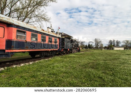 Side view of black old train wagon, in cloudy sky. - stock photo