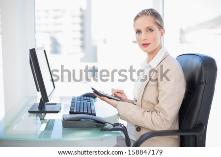 Side view of blonde businesswoman using calculator in bright office