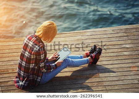 Side view of blonde hair woman using digital tablet while sitting on a wooden pier next to the sea, female tourist busy use tablet while sitting outdoors at sunny day, girl browsing outside, flare sun - stock photo