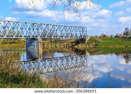 Side view of blue steel bridge on a river with reflection of cloudy blue sky among meadow area. - stock photo