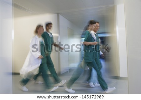Side view of blurred physicians rushing through hospital corridor