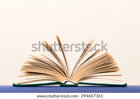 Side view of book open in shape of hand-held fan, on light background