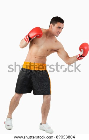 Side view of boxer performing uppercut against a white background - stock photo