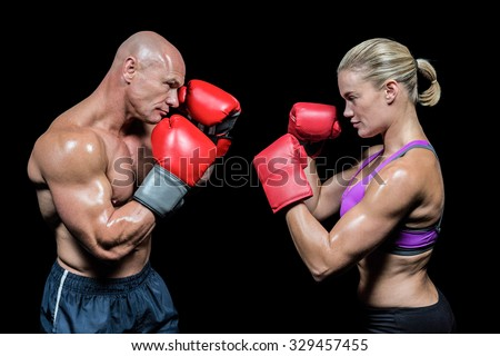 Side view of boxers with fighting stance against black background - stock photo