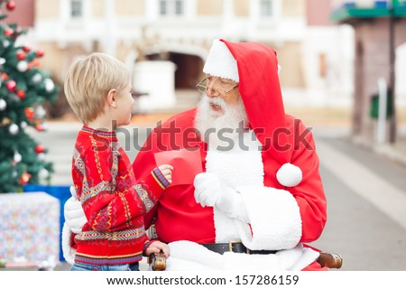 Side view of boy giving wish list to Santa Claus in courtyard - stock photo