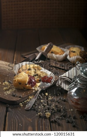 Side view of broken cupcake with chocolate drops and jar with jam, make in dark tonality - stock photo