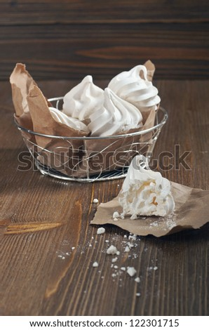 Side view of broken meringue with crumbs on paper and lot of meringues in iron bowl on dark wooden background - stock photo