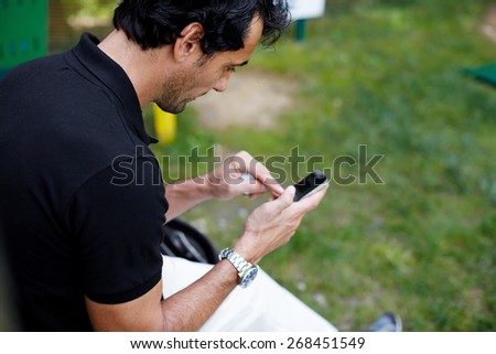 Side view of brunette hair mature man typing message on mobile phone, people using technology everywhere, man typing text on smart phone outdoors, focus on the face - stock photo
