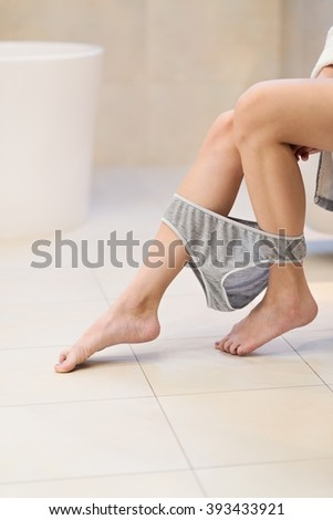 Side view of brunette woman sitting on toilet in the bathroom. - stock photo