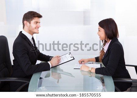 Side view of business colleagues with clipboards discussing at desk in office - stock photo