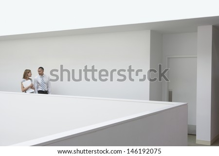 Side view of business couple walking through office hallway side view - stock photo