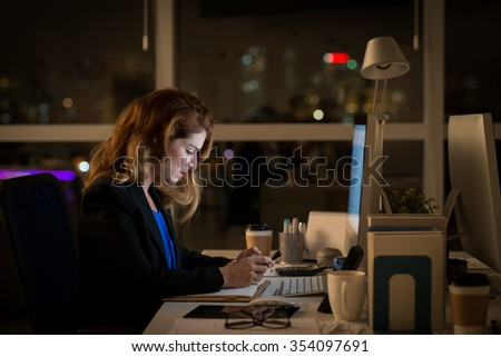 Side view of business lady working in the office late at night - stock photo