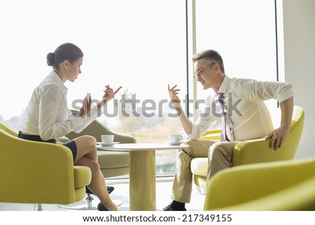 Side view of business people conversing at lobby - stock photo