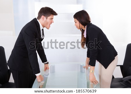 Side view of business people quarreling at desk in office