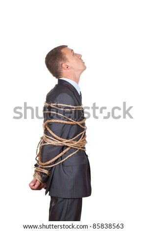 Side view of businessman executive tied up with rope, looking up - stock photo