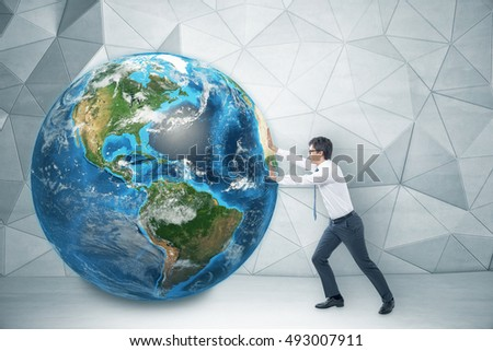 Side view of businessman in glasses pushing the globe in room with concrete walls and geometric ornament. Concept of large project.