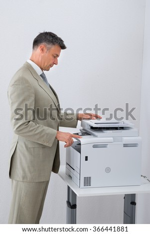 Side view of businessman keeping paper on photocopy machine in office