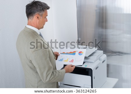 Side view of businessman looking at paper with graphs while standing by color printer - stock photo
