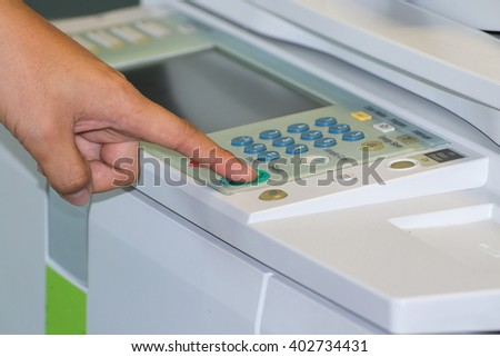 SIde view of businessman pressing printer's button at work